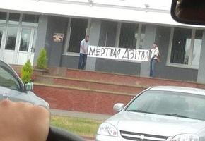 Возле Лидского райисполкома двое людей с плакатом «Мёртвая Дзiтва» высказали публичный протест